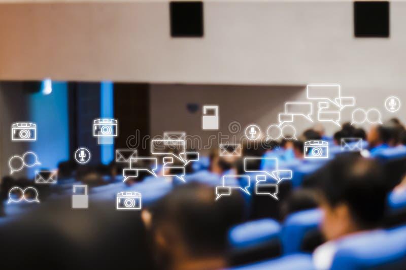 Vista posterior de la audiencia que asiste que hace frente a seminario del negocio en la sala de conferencias con los iconos soci imagenes de archivo