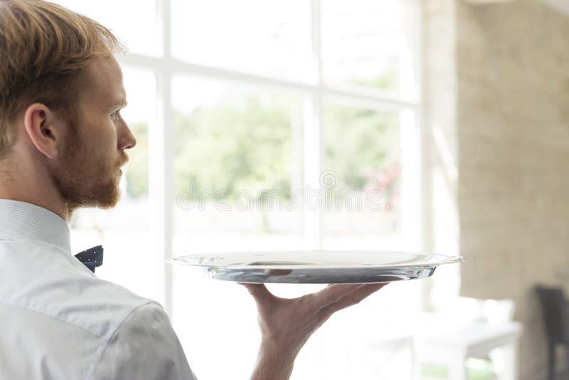 Vista posterior de la bandeja joven confiada de la tenencia del camarero mientras que se coloca en el restaurante fotografía de archivo libre de regalías