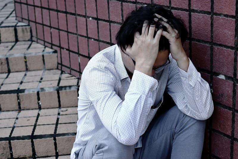 Vista posterior de la cara asiática joven de la cubierta del hombre de negocios de la ansiedad confusa con las manos fotografía de archivo