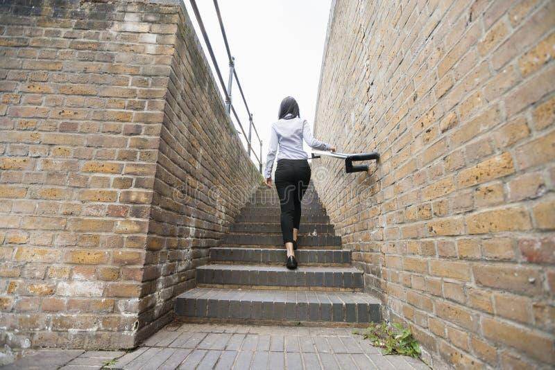 Vista posterior de la empresaria asiática joven que camina encima de las escaleras foto de archivo libre de regalías