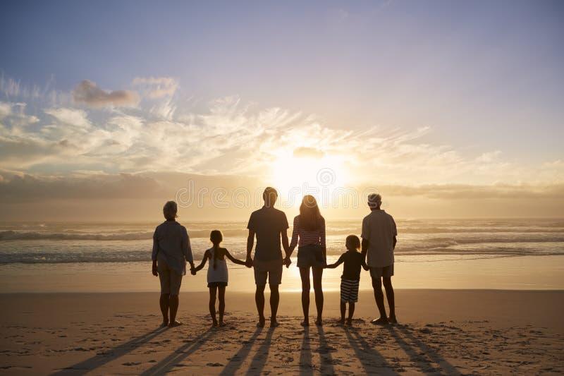 Vista posterior de la familia multi de la generación silueteada en la playa foto de archivo libre de regalías