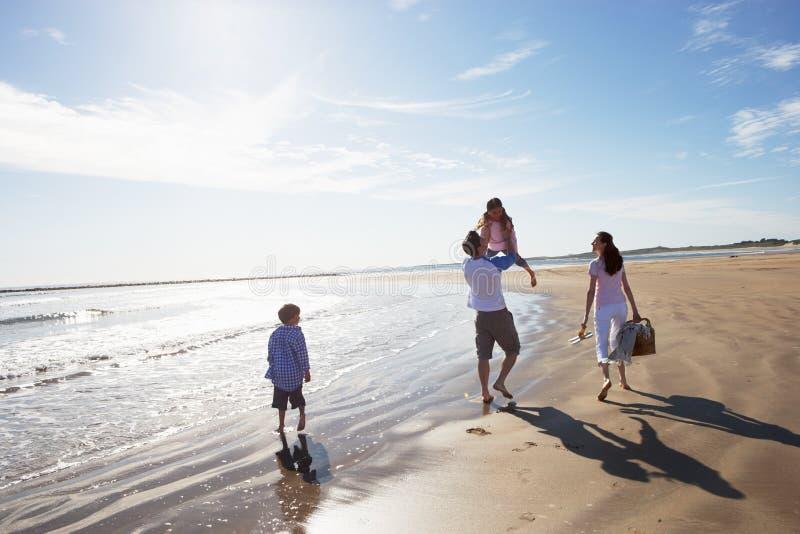 Vista posterior de la familia que camina a lo largo de la playa con la cesta de la comida campestre fotos de archivo libres de regalías