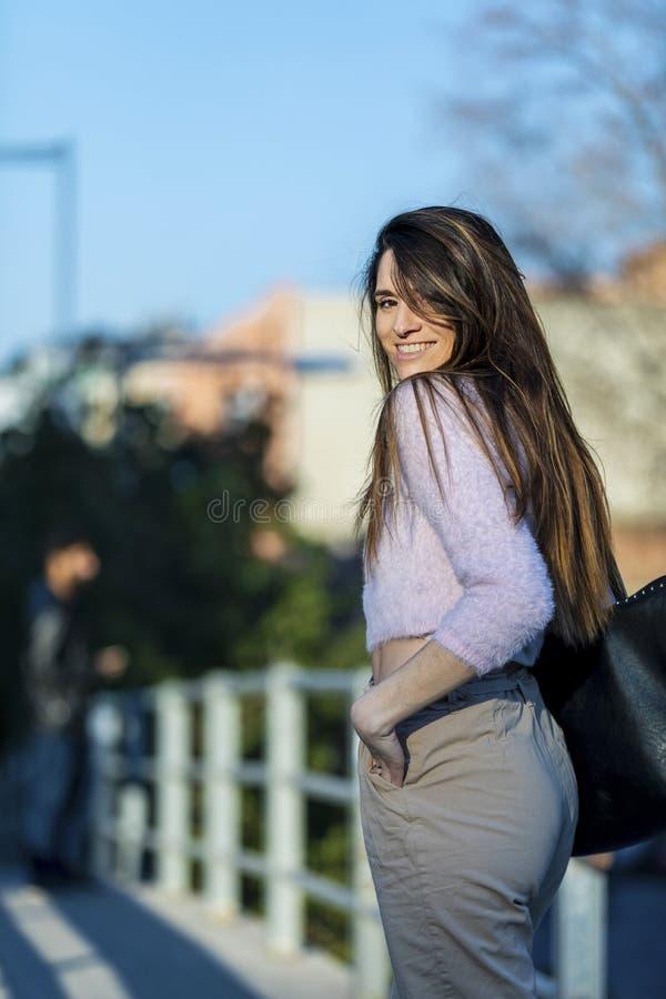 Vista posterior de la mano hermosa sonriente de la mujer joven en el bolsillo que se coloca en la calle mientras que mira lejos e foto de archivo libre de regalías