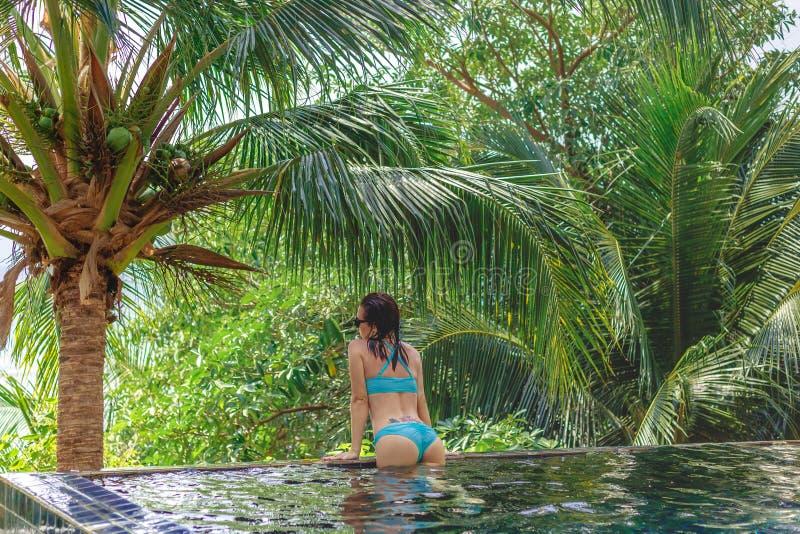 vista posterior de la muchacha atractiva en inclinarse del bikini fotografía de archivo
