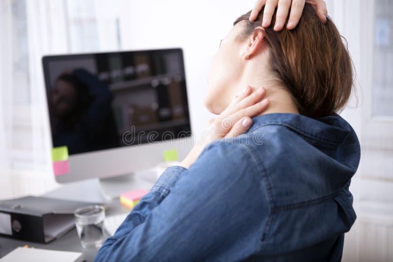 Vista posterior de la mujer cansada de la oficina que da masajes a su cuello imágenes de archivo libres de regalías
