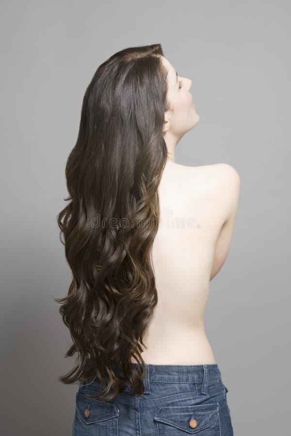 Vista posterior de la mujer con las tetas al aire con el pelo ondulado largo fotografía de archivo libre de regalías