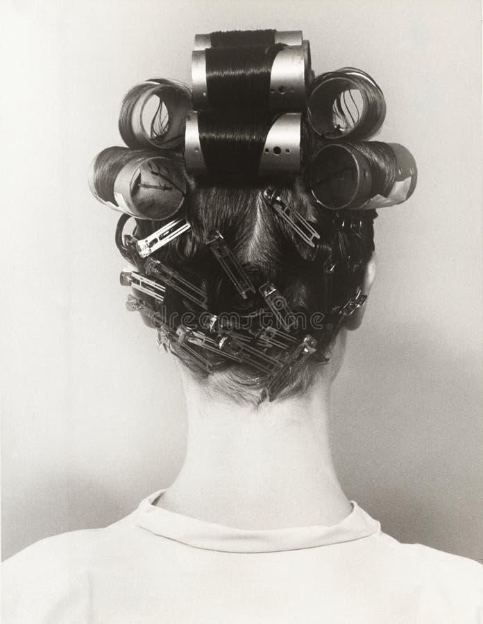 Vista posterior de la mujer con los bigudíes en su pelo imagenes de archivo