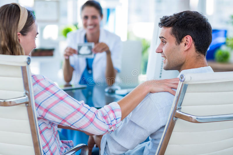 Vista posterior de la mujer embarazada y su del marido que discuten con el doctor fotografía de archivo