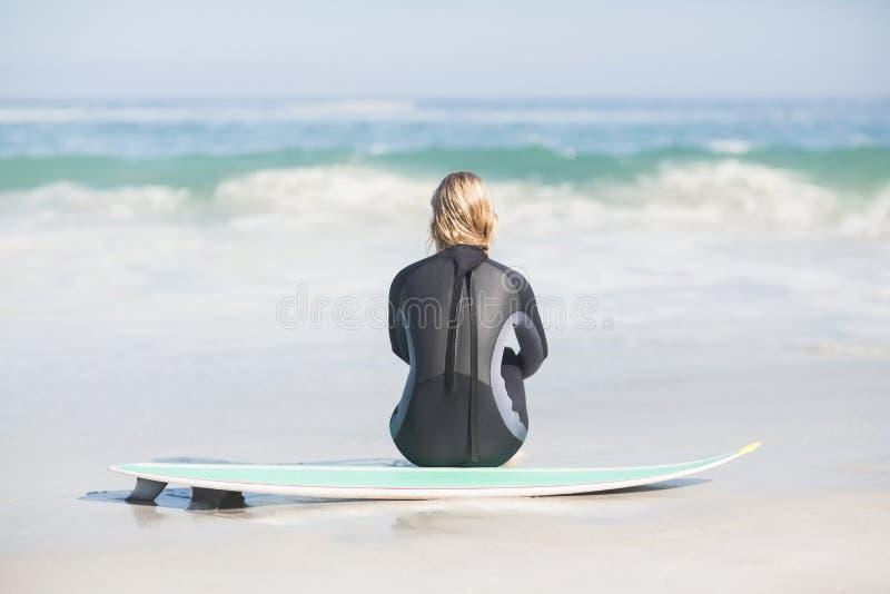 Vista posterior de la mujer en el wetsuit que se sienta con la tabla hawaiana en la playa imagen de archivo libre de regalías