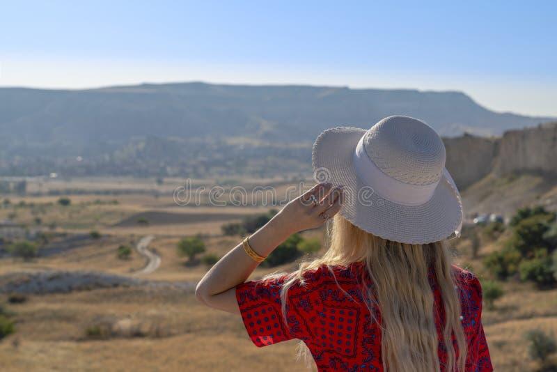 Vista posterior de la mujer joven del sombrero blanco que mira el camino y que cuenta con alguien La mujer aguarda la llegada de  imágenes de archivo libres de regalías