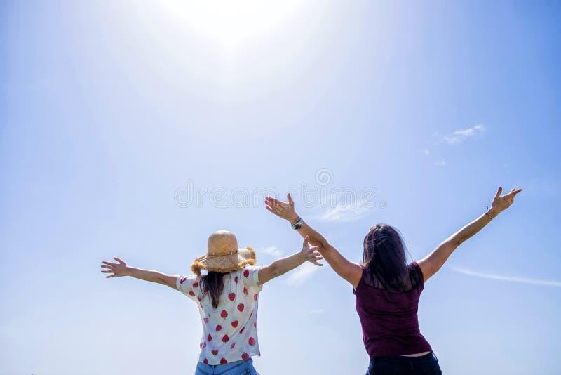 Vista posterior de la mujer joven dos que se sienta en una cerca con los brazos aumentados contra el cielo azul imágenes de archivo libres de regalías