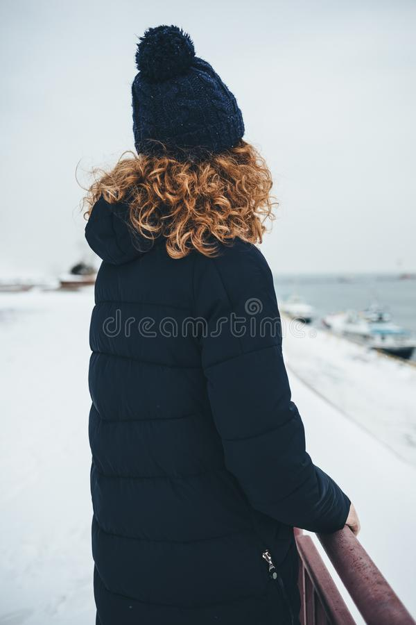 Vista posterior de la mujer joven que lleva la capa caliente fotografía de archivo