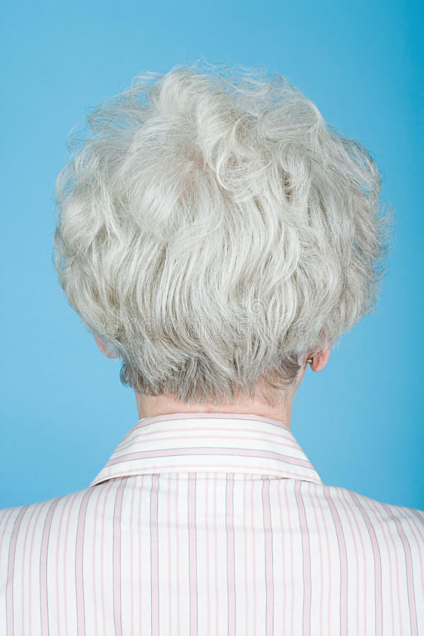 Vista posterior de la mujer mayor fotos de archivo