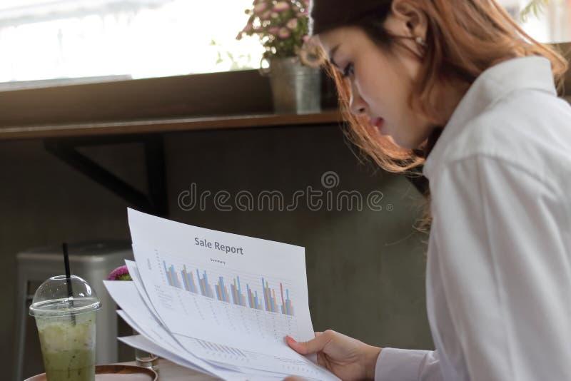 Vista posterior de la mujer de negocios asiática joven confiada que analiza cartas o papeleo en la oficina Foco selectivo y profu imagen de archivo