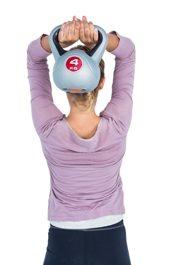 Vista posterior de la mujer que ejercita con el kettlebell foto de archivo libre de regalías
