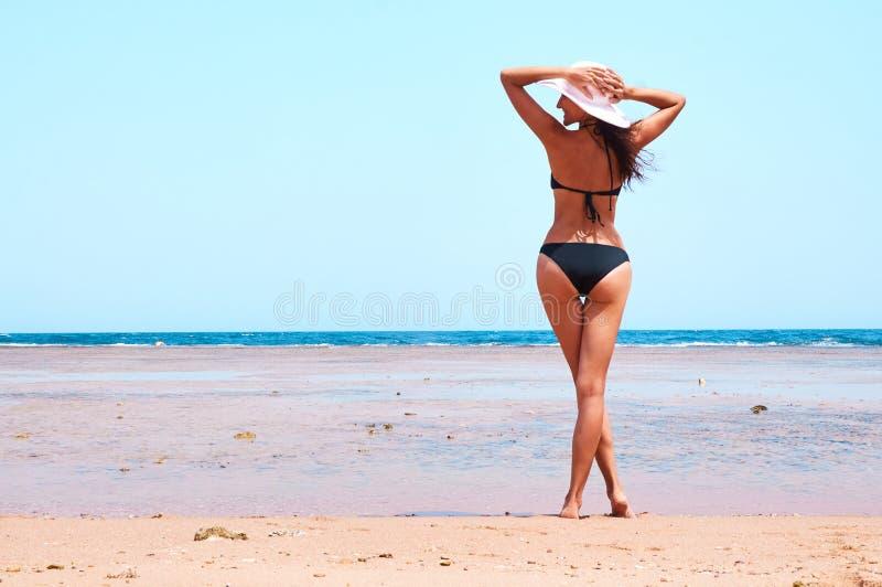 Vista posterior de la mujer sonriente que se coloca en la playa imagen de archivo libre de regalías