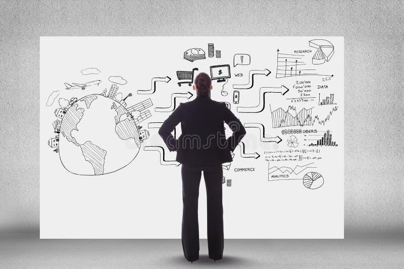 Vista posterior de la persona del negocio que mira iconos y el texto en la cartelera imagen de archivo