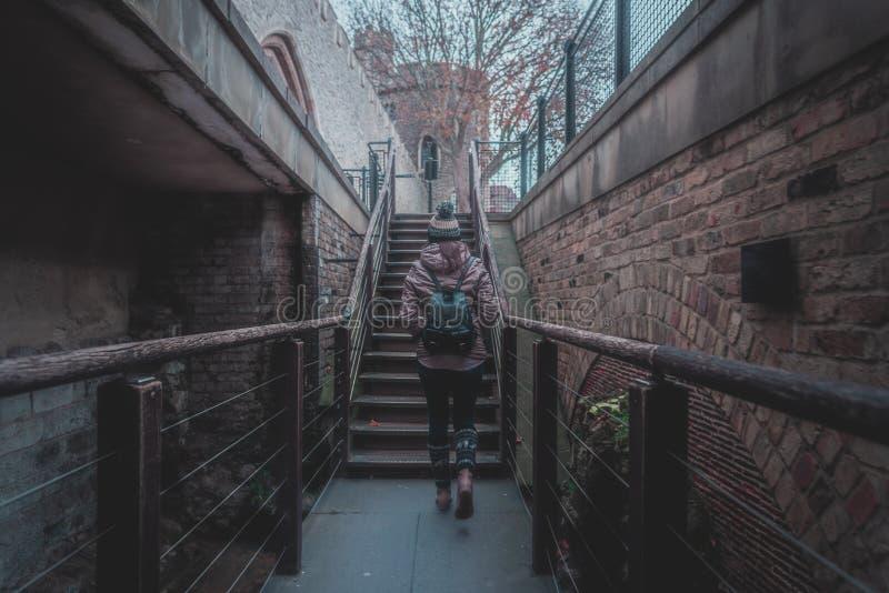 Vista posterior de la silueta de la mujer joven que camina a través de una escalera entre las paredes de ladrillo viejas de un ca imagenes de archivo