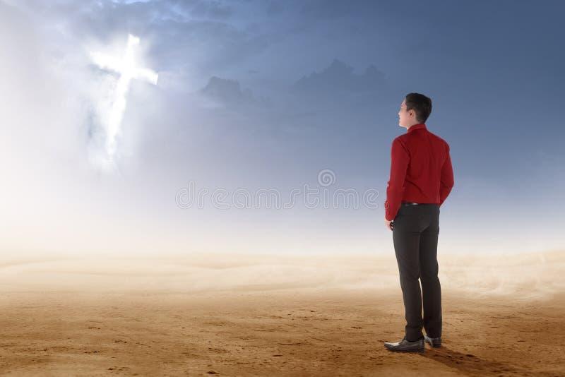 Vista posterior de la situación asiática del hombre de negocios en desierto y de mirar la cruz cristiana que brilla intensamente fotografía de archivo libre de regalías