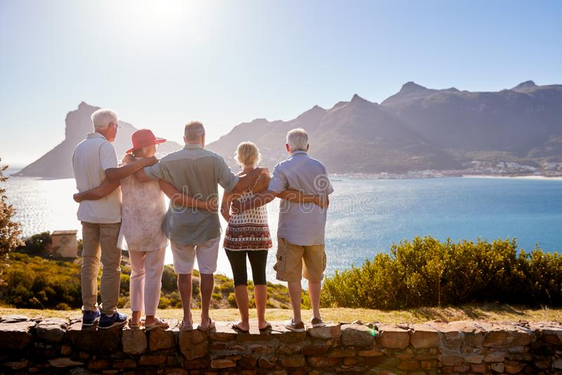 Vista posterior de los amigos mayores que visitan la señal turística el las vacaciones del grupo que se colocan en la pared imágenes de archivo libres de regalías