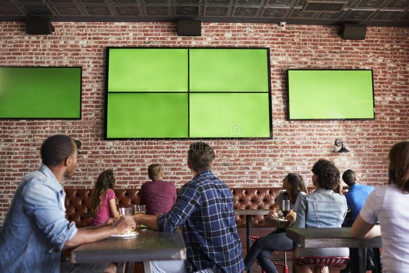 Vista posterior de los amigos que miran el juego en barra de deportes en las pantallas imagen de archivo libre de regalías