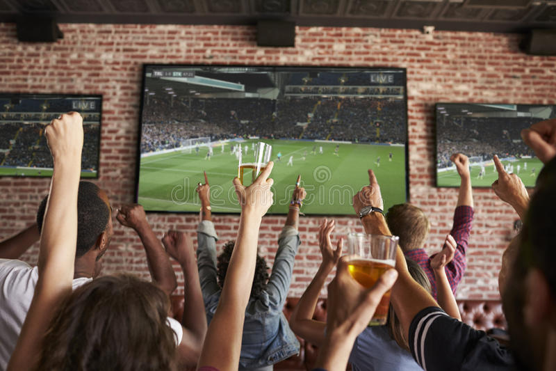 Vista posterior de los amigos que miran el juego en barra de deportes en las pantallas foto de archivo libre de regalías