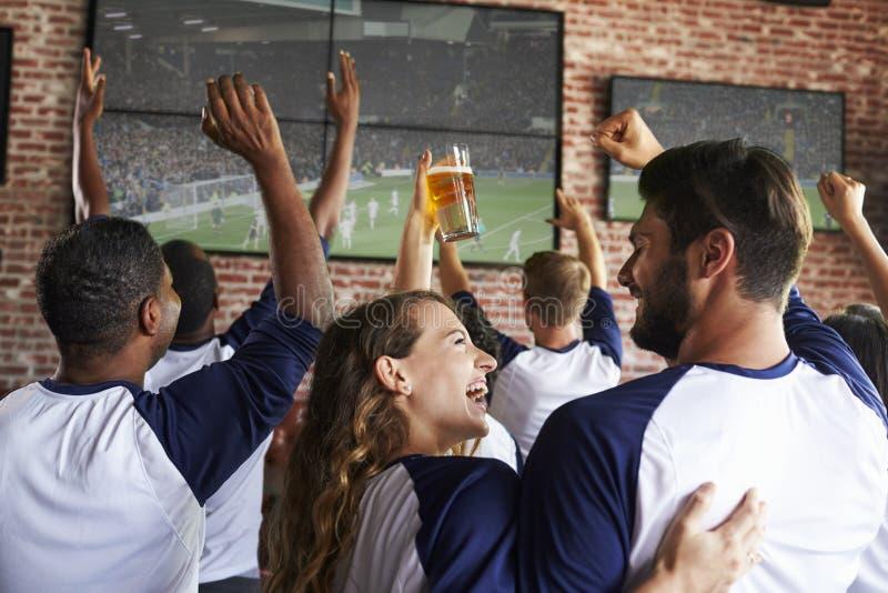Vista posterior de los amigos que miran el juego en barra de deportes en las pantallas fotos de archivo libres de regalías