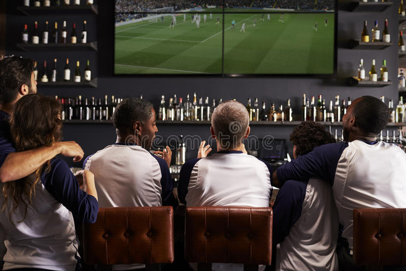 Vista posterior de los amigos que miran el juego en la celebración de la barra de deportes foto de archivo