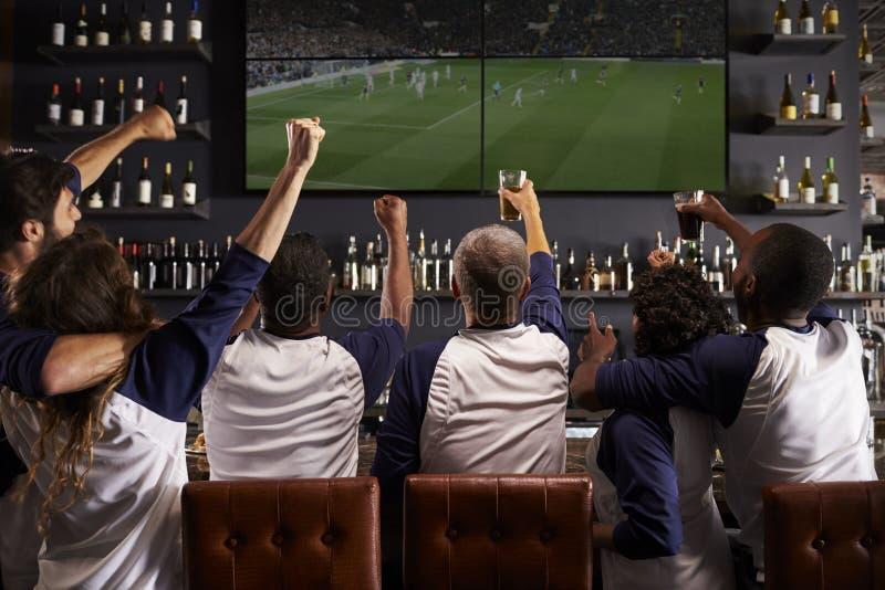 Vista posterior de los amigos que miran el juego en la celebración de la barra de deportes imagenes de archivo