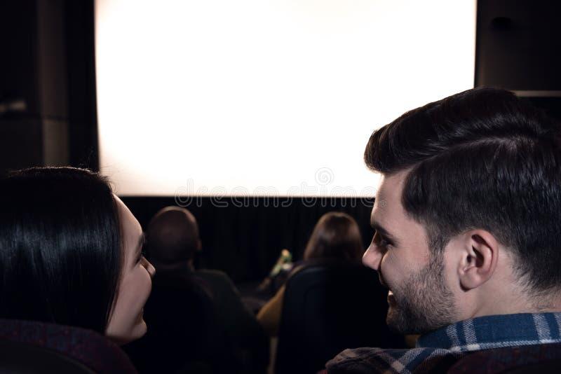 vista posterior de los amigos que se sientan en cine con el espacio en blanco blanco fotografía de archivo libre de regalías