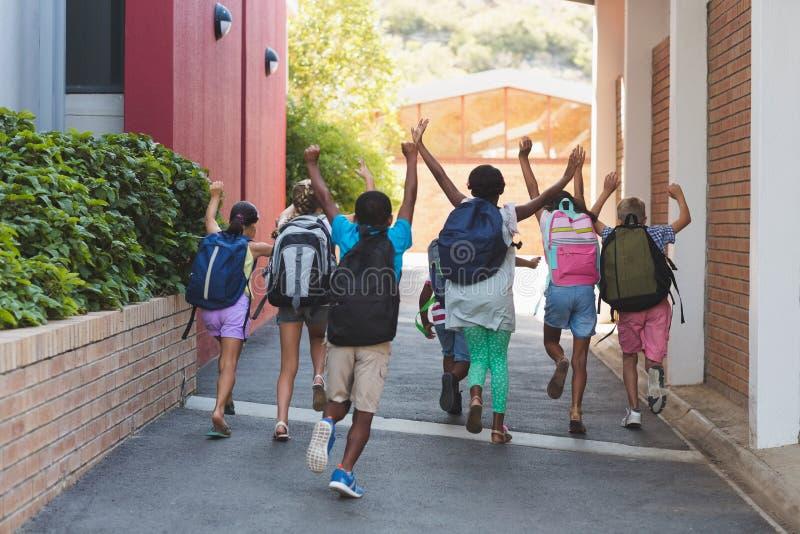 Vista posterior de los compañeros de clase que corren en el campus de la escuela imagen de archivo libre de regalías