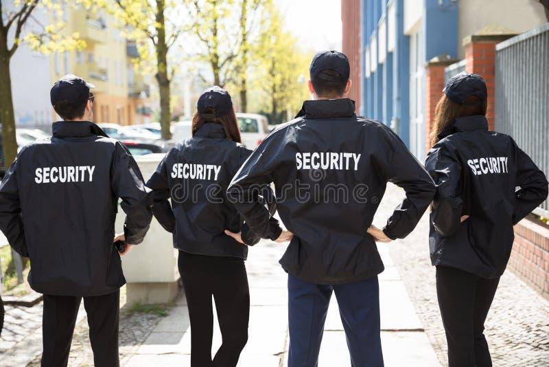 Vista posterior de los guardias de seguridad que se colocan en fila fotos de archivo libres de regalías