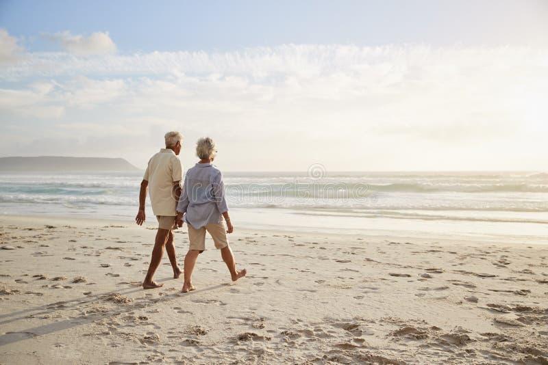 Vista posterior de los pares mayores que caminan a lo largo de la playa de común acuerdo imagenes de archivo