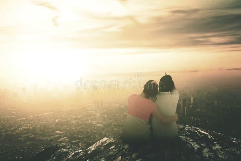 Vista posterior de los pares que se sientan encima de la montaña para ver puesta del sol fotografía de archivo