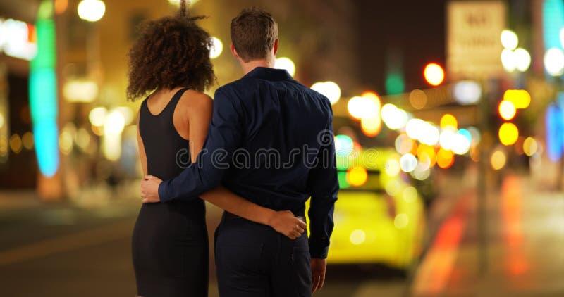 Vista posterior de los pares románticos que miran nightlights de la ciudad foto de archivo