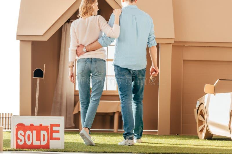vista posterior de los recienes casados que caminan a su nuevo fotografía de archivo libre de regalías