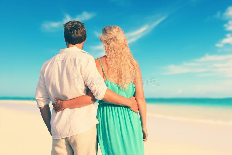 Vista posterior de pares con los brazos alrededor en la playa imágenes de archivo libres de regalías