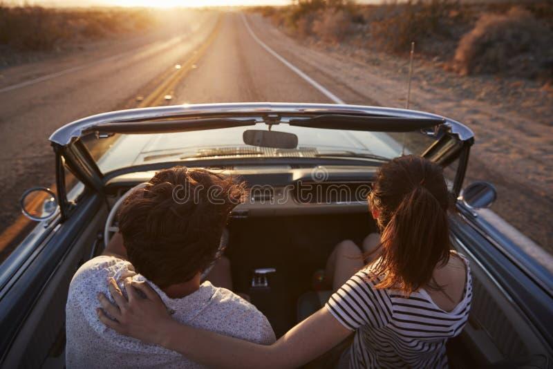 Vista posterior de pares en el viaje por carretera que conduce el coche convertible clásico hacia puesta del sol foto de archivo libre de regalías
