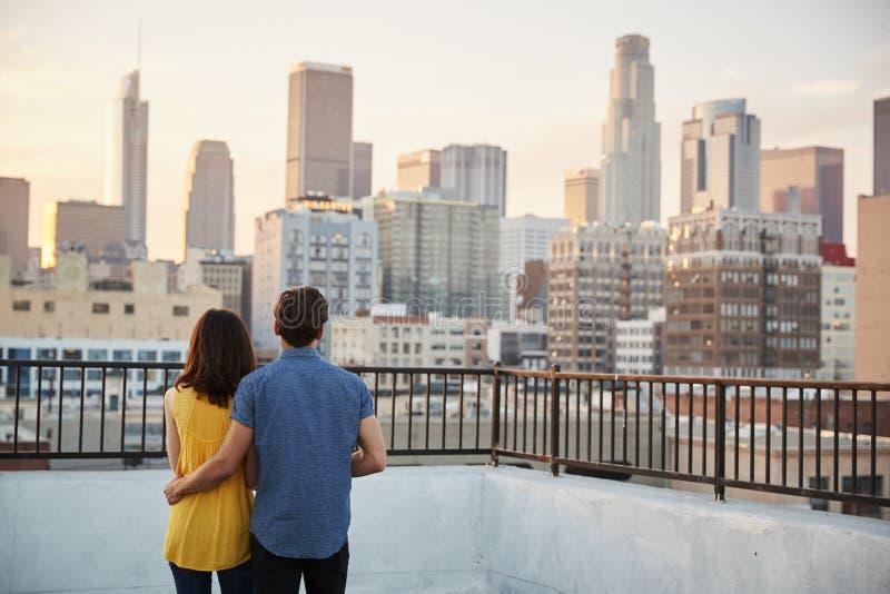 Vista posterior de pares en la terraza del tejado que considera hacia fuera sobre horizonte de la ciudad la puesta del sol fotos de archivo