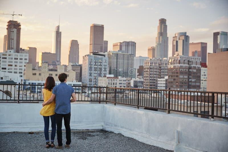Vista posterior de pares en la terraza del tejado que considera hacia fuera sobre horizonte de la ciudad la puesta del sol foto de archivo