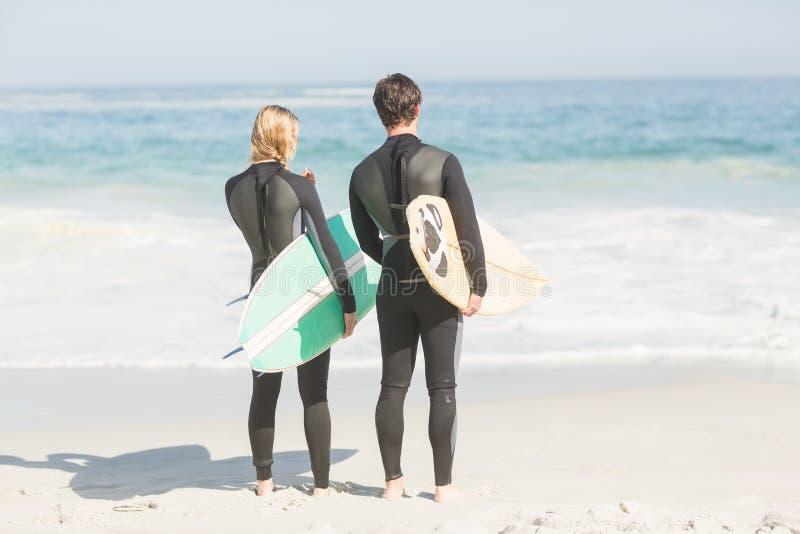 Vista posterior de pares en wetsuit con la tabla hawaiana que se coloca en la playa fotos de archivo libres de regalías