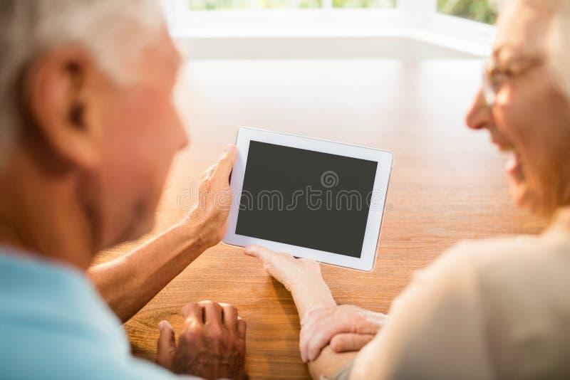 Vista posterior de pares mayores usando la tableta imagenes de archivo