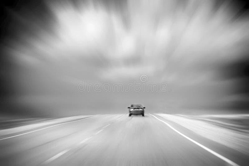 Vista posterior de un coche que apresura en la carretera de asfalto en campo Cielo nublado, tempestuoso Imagen blanco y negro con fotos de archivo libres de regalías