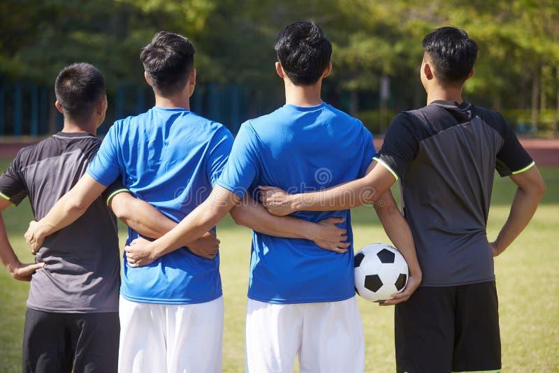 Vista posterior de un equipo de jugadores de fútbol asiáticos imágenes de archivo libres de regalías