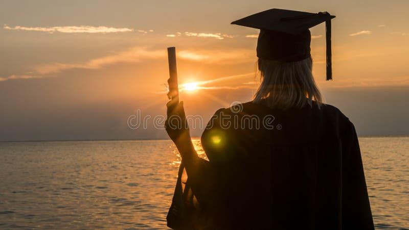 Vista posterior de un graduado de universidad con un diploma en su mano en un fondo de la puesta del sol sobre el mar Nuevas opor foto de archivo libre de regalías
