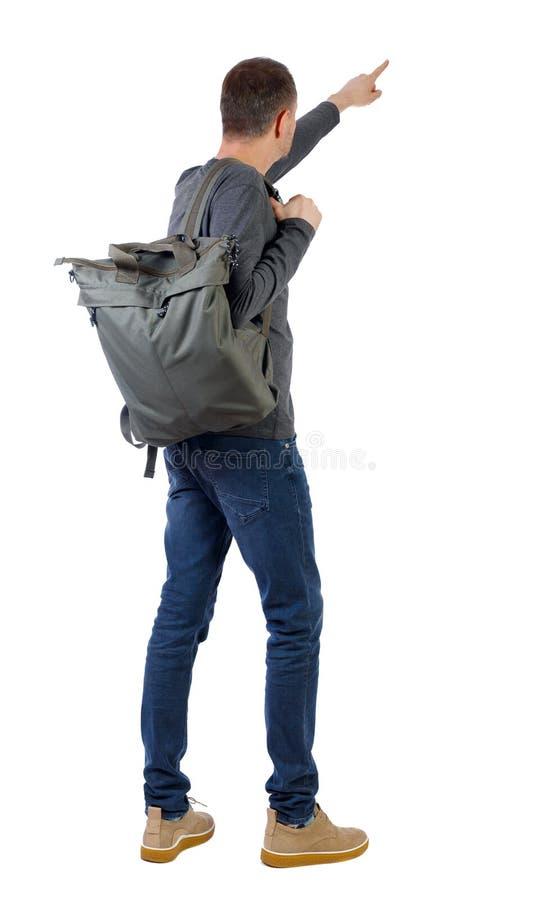 Vista posterior de un hombre con una mochila verde apuntando hacia adelante imagen de archivo
