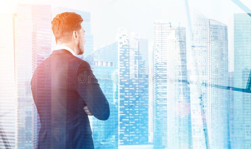Vista posterior de un hombre de negocios que mira la ciudad de su oficina, skys foto de archivo