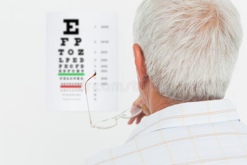Vista posterior de un hombre mayor que mira la carta de ojo imagenes de archivo