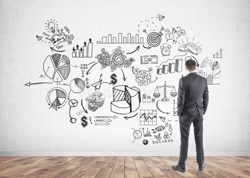 Vista posterior de un hombre de negocios que mira bosquejo del plan imagenes de archivo