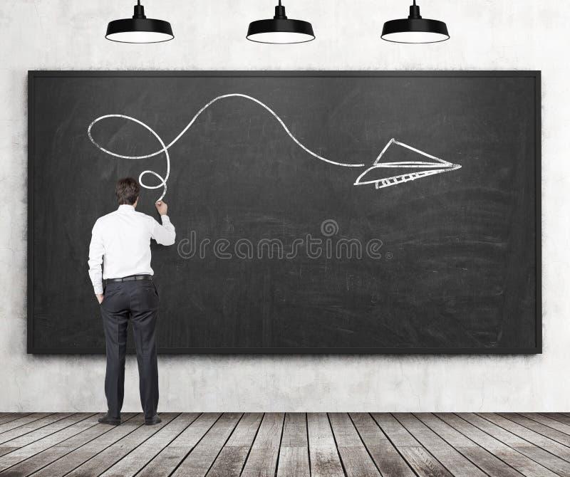 Vista posterior de un hombre que está dibujando una flecha como concepto de solución posible del problema complicado Pizarra negr imagenes de archivo